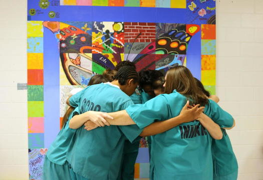 Incarcerated women who participated in the Prisoners Too art project hug in front of the installation at a South Carolina prison. (South Carolina Department of Corrections)<br />