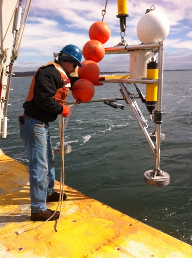 PHOTO: A University of Connecticut researcher places equipment in Long Island Sound to measure temperature, sea level pressure and waves to create maps which will predict coastal flooding. Photo credit: Mary M. Howard-Strobel.