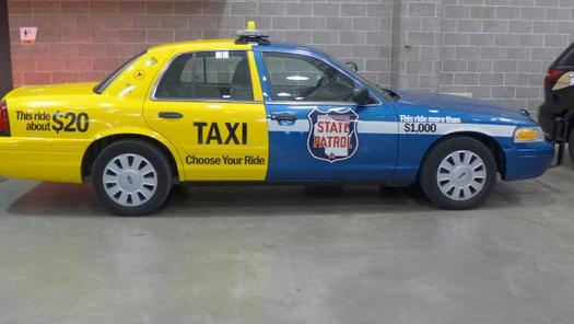 PHOTO: This car was painted up by Wisconsin law enforcement authorities to graphically demonstrate the difference in dollar cost between taking a taxi home after having had too much to drink, rather than put the public at risk by drunken driving and getting arrested for it. (Photo credit: Gilman Halsted, WPR)