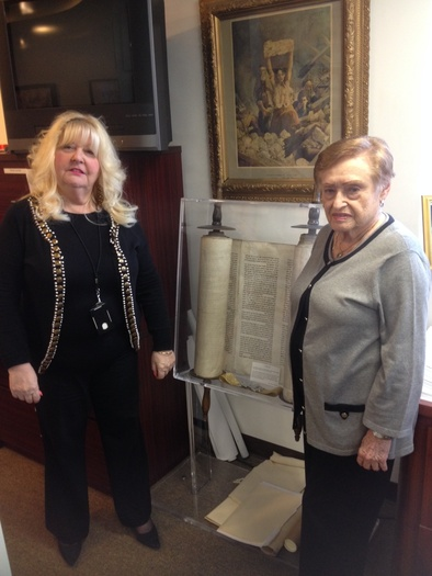 PHOTO: Rositta Kenigsberg and Rita Hofrichter stand in front of one of the Holocaust Documentation and Education Center's most prized possessions: a Torah rescued from a Czechoslovakian synagogue destroyed during the Nazi occupation of World War II. Photo credit: Phil Latzman