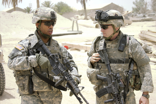 An African American soldier and white soldier working together. Credit: Rockfinder.
