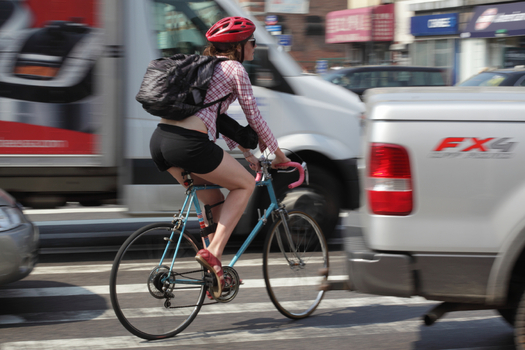Female cyclist in heavy traffic during rush hour. Credit: Andrew Cribb.