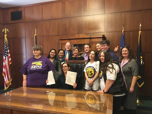 PDX worker Kasil Kapriel, third from left, was at the signing of a bill to raise Oregon's minimum wage this month. (SEIU Local 49)