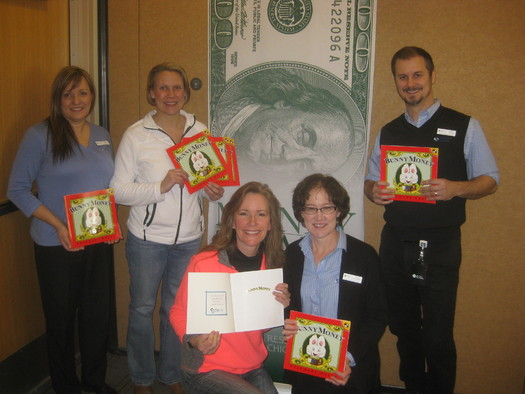 """Employees of Community Financial Credit Union help unload donated copies of the book """"Bunny Money"""" at the Novi library, one of many Money Smart Kids Read locations. (B. Troost/MCUL)"""