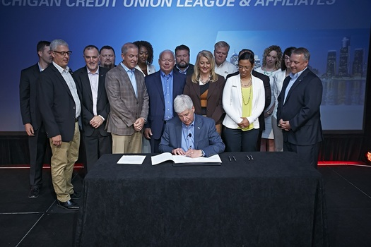 Flanked by Michigan credit union leaders, Gov. Rick Snyder signed an update of the Michigan Credit Union Act into law. (L. Michels/MCUL)