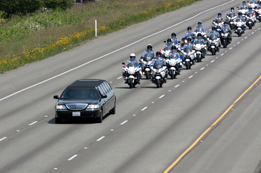 Police on motorcycle escort a hearse carrying a fallen police officer at a recent funeral. (njp/iStockphoto)
