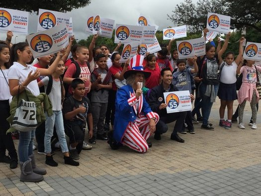 Dressed as Uncle Sam, Andrew Tonkovich, a lecturer in writing, poses with schoolchildren and Mayor Bao Nguyen of Garden Grove at a Prop 55 event at UC-Irvine on Monday. (Fred Glass/California Federation of Teachers)