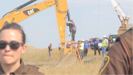 Happi American Horse chains himself to construction equipment at an August protest of the Dakota Access Pipeline. (Desiree Kane/Wikimedia Commons)