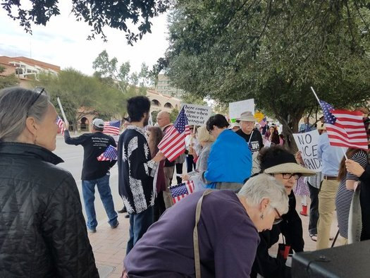 Protesters sang patriotic songs in front of Sen. John McCain's office in Tucson to protest immigration raids. (Indivisible Southern Arizona)