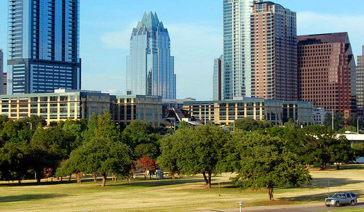 A stand of live oak trees in Butler Park frames the downtown Austin skyline. Conservationists say urban forests are critical to air and water quality in Texas cities. (Wikimedia Commons)