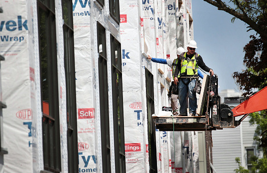 Construction workers put the finishing touches on new townhouses in Dallas. The high cost of housing is making it difficult for low-income Texans to find an affordable home. (ScottOlson/Getty Images)