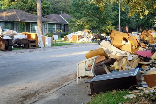 Flood damage debris lines a Houston residential street following Hurricane Harvey in 2017. More than 200,000 homes and businesses along the Texas Gulf Coast were damaged or destroyed by the storm. (IrinaK/AdobeStock)