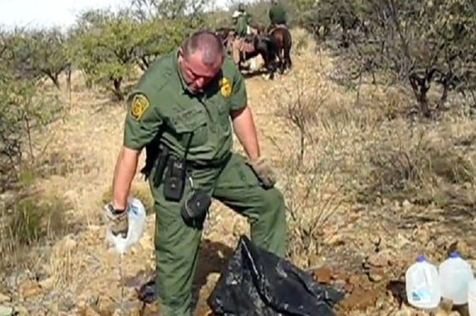 A U.S. Border Patrol officer opens and drains a water bottle left by No More Deaths volunteers to help migrants in the Agua Prieta National Wildlife Refuge in 2017. (NoMoreDeaths)