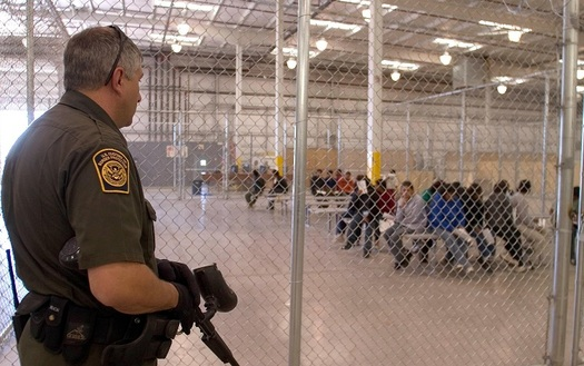 A U.S. Border Patrol agent guards migrants at one of several detention centers along the U.S.-Mexico border. (US Border Patrol and Immigration)