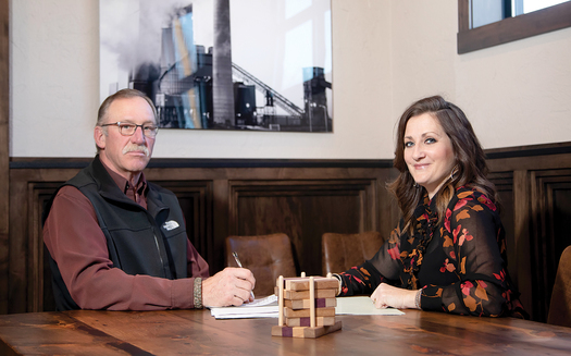 Christie Obenauer (R), president and CEO of Union State Bank of Hazen, meets with Matt Clarys (L) of Western Steel Builders. Partnering with the Bank of North Dakota, Obenauer's small bank has been able to finance several large projects in her town. (Justine Wiedrich)