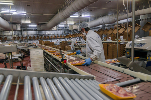 Tight working conditions on production lines in meat and poultry processing facilities make it impossible for workers to adhere to 6-foot distancing. (Adobe Stock)