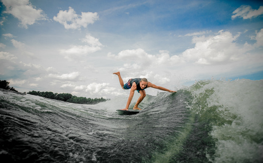 Wakesurfing requires a large wake behind a boat. A study is underway to determine the possible impact of those big waves, and other recreational boating, on lake and shoreline health in Minnesota.  (Adobe Stock)