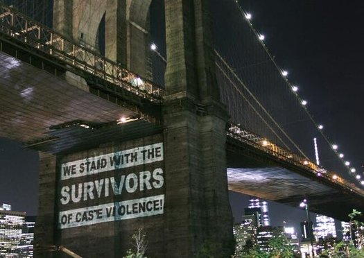 Groups projected their support for survivors of caste-based violence on the Brooklyn Bridge in 2015. (Thenmozi Soundararajan)