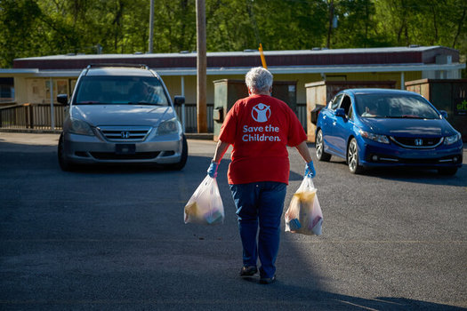 At a drive-up distribution, a Save the Children staff member hand-delivers food to children and families. (Shawn Millsaps/Save the Children)