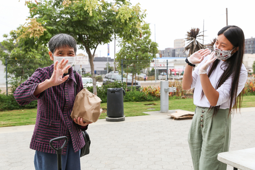 A local resident waves as she picks up her bag of produce from the Chinatown Health Initiative at the Los Angeles State Historic Park. (Veronica Monjara/Las Fotos)