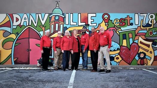 AARP volunteers pose in front of the downtown Danville Community Challenge mural in 2018. (Adobe Stock)