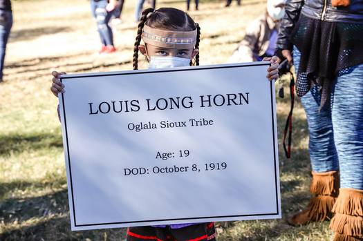 A young girl holds the name of an Indigenous teen tied to a former Native American boarding school in Rapid City. (SiouxSanLands)