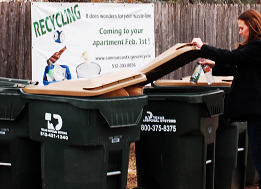 Katie Weatherby recycles plastic bottles in the recycling bins provided by her San Marcos apartment complex, Hillside Ranch. Photo credit: Erin Dyer