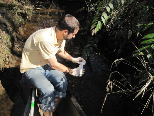 Photo: Carson collecting samples from the French Broad River. Courtesy: Hartwell Carson