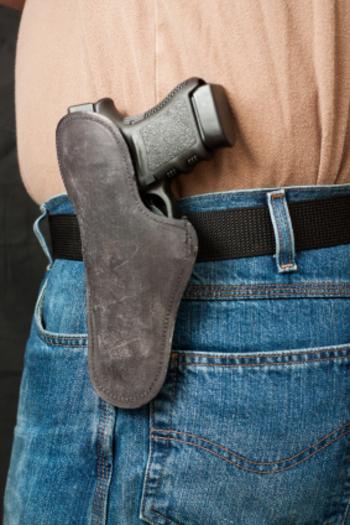 Pistola en su funda, en el cinto.