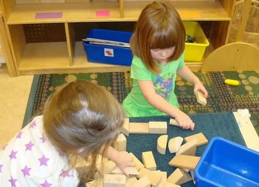 PHOTO: Child care is a major expense in Illinois family budgets, and a new report finds the cost of day care grew up to eight times faster than the average family's income in 2012. Photo: girls playing with blocks. Credit: M.Kuhlman