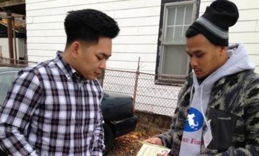 """PHOTO: A canvasser from the Cambodian Mutual Assistance Association talks to a resident about open enrollment and his health care options in Lowell, MA as part of Health Care For All's campaign """"Apply Now, Stay Covered"""" Photo courtesy Cambodian Mutual Assistance Association."""