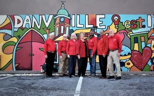 AARP volunteers pose in front of the downtown Danville Community Challenge mural in 2018. (Adobe Stock)<br />