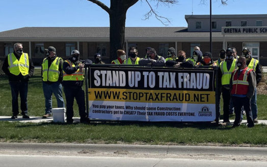 Workers protest tax fraud in the construction field at a school administration building in Gretna, Neb. (Eric Leanos/NCSRCC)