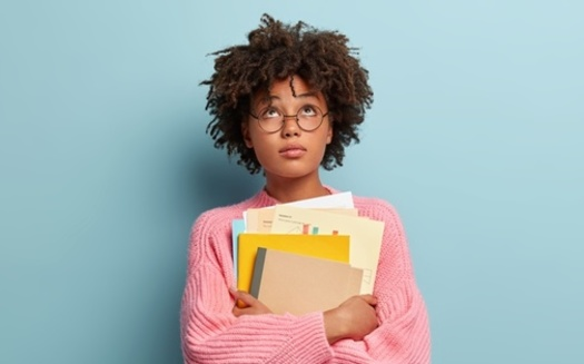 Black women carry roughly 20% more student debt than their white counterparts. (Adobe Stock)