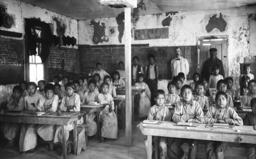 Native American students, most of them barefoot, sit for lessons in a crowded classroom inside the Walapai Indian School in Kingman, Ariz., circa 1900. (Wikimedia Commons)