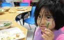 PHOTO: A Minnesota student enjoys locally grown green beans as part of a Farm to Preschool celebration. Photo courtesy of Institute for Agriculture and Trade Policy.