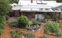 This backyard includes edible landscaping, a passive solar retrofit and a 6,500-gallon rainwater catchment system. In 2000, it was a conventional lawn. Credit: Northwest Permaculture Convergence.