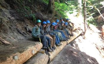 PHOTO: There isn't much time for sitting as a member of this youthful crew working to relocate the Kelly Creek Trail in the Mount Baker-Snoqualmie National Forest. It's one of 50 projects across the country to commemorate the 50th anniversary of the Wilderness Act. Photo courtesy of Northwest Youth Corps.