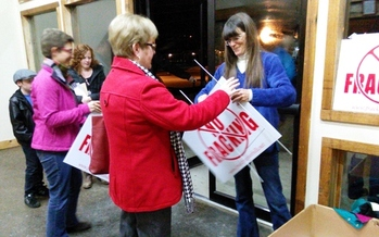 PHOTO: A citizen picks up a sign in opposition to hydraulic fracking in Kentucky as she leaves an informational meeting about the technology. Photo by Greg Stotelmyer.