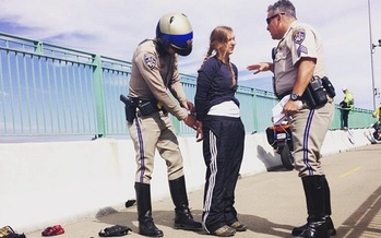 Activist Emily Heffling of the group ForestEthics is detained Monday for trying to hang an anti-oil train banner on the Benicia-Martinez railroad bridge east of Vallejo. Credit: Jay Carmona/ForestEthics.