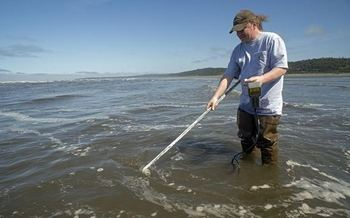 Scott Mazzone, a marine biologist with the Quinault Indian Nation, takes water quality samples. Credit: Debbie Ross-Preston, NW Indian Fisheries Commission.