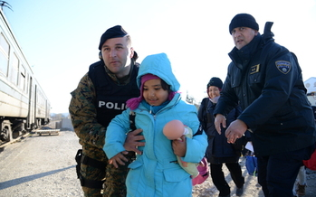 Macedonia police agents help a refugee mother and daughter in transit through the European country. (New Partners)
