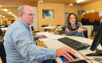 Idaho's 2015 Andrus Award winner, Duane Brown, helps a client of the AARP Foundation's Tax Aide program. (AARP Idaho)
