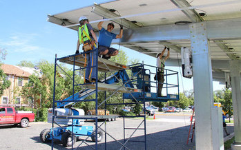 Workers install a new solar panel array at the