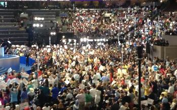 Delegates crowd the stage at the Democratic National Convention, many carrying signs that say