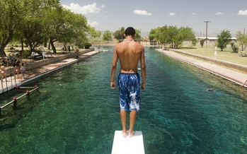 A swimmer prepares to dive into the cold, clear water of the pool at Balmorhea State Park. (Texas Parks and Wildlife photo)