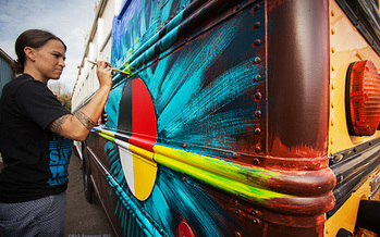 Native American artist Clay with the Native American Youth and Family Center provides a mural for a side of the Bunk Bus. (Rick Rappaport)