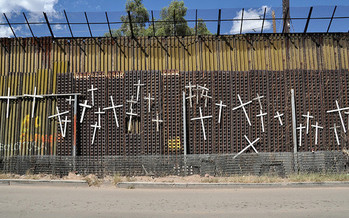 Crosses on the border fence with Mexico honor people's lives lost crossing into the United States. (Jonathan McIntosh/Creative Commons/Flickr)