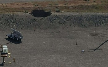 A large hole, seen at the top of the picture, developed over a tunnel at the Hanford site. The tunned contains rail cars containing radioactive waste. (U.S. Department of Energy)