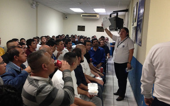 Deportees from the United States crowd into a small room to receive information from an immigration official in El Salvador. (Fronteras Desk/flickr)